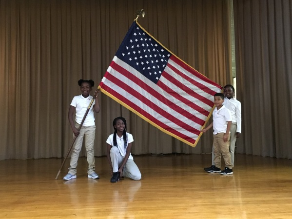 Four students holding U.S. flag and standing on stage