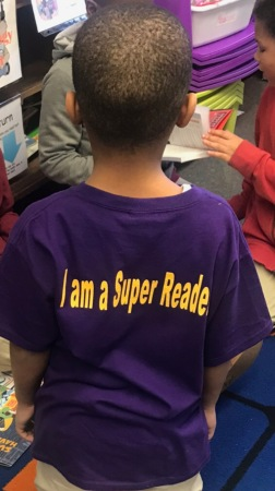 "Student with back of t-shirt showing that says ""I am a super reader."""