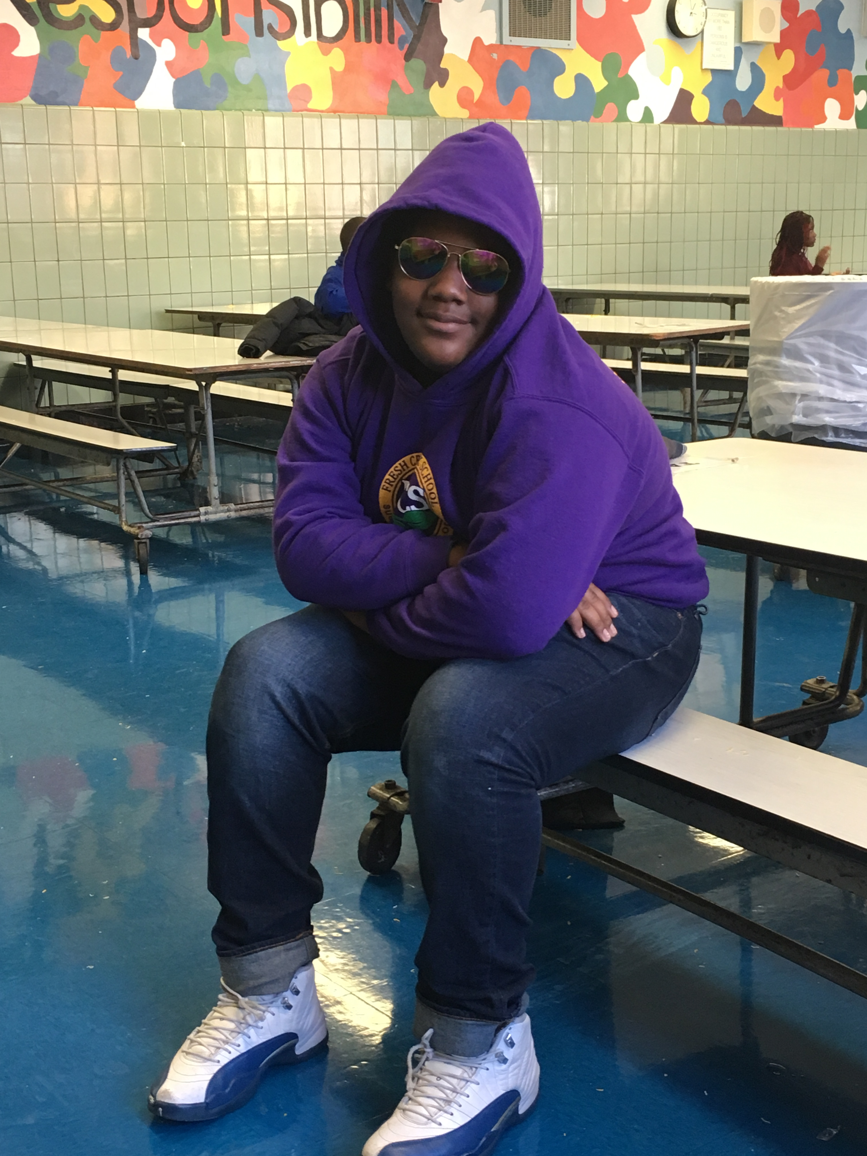 Student sitting at cafeteria table with sunglasses on and smiling at the camera
