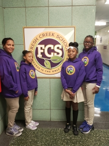 Four students smiling at camera in front of FCS sign