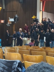 Group of young and older MBK participants standing on stage and talking to each other