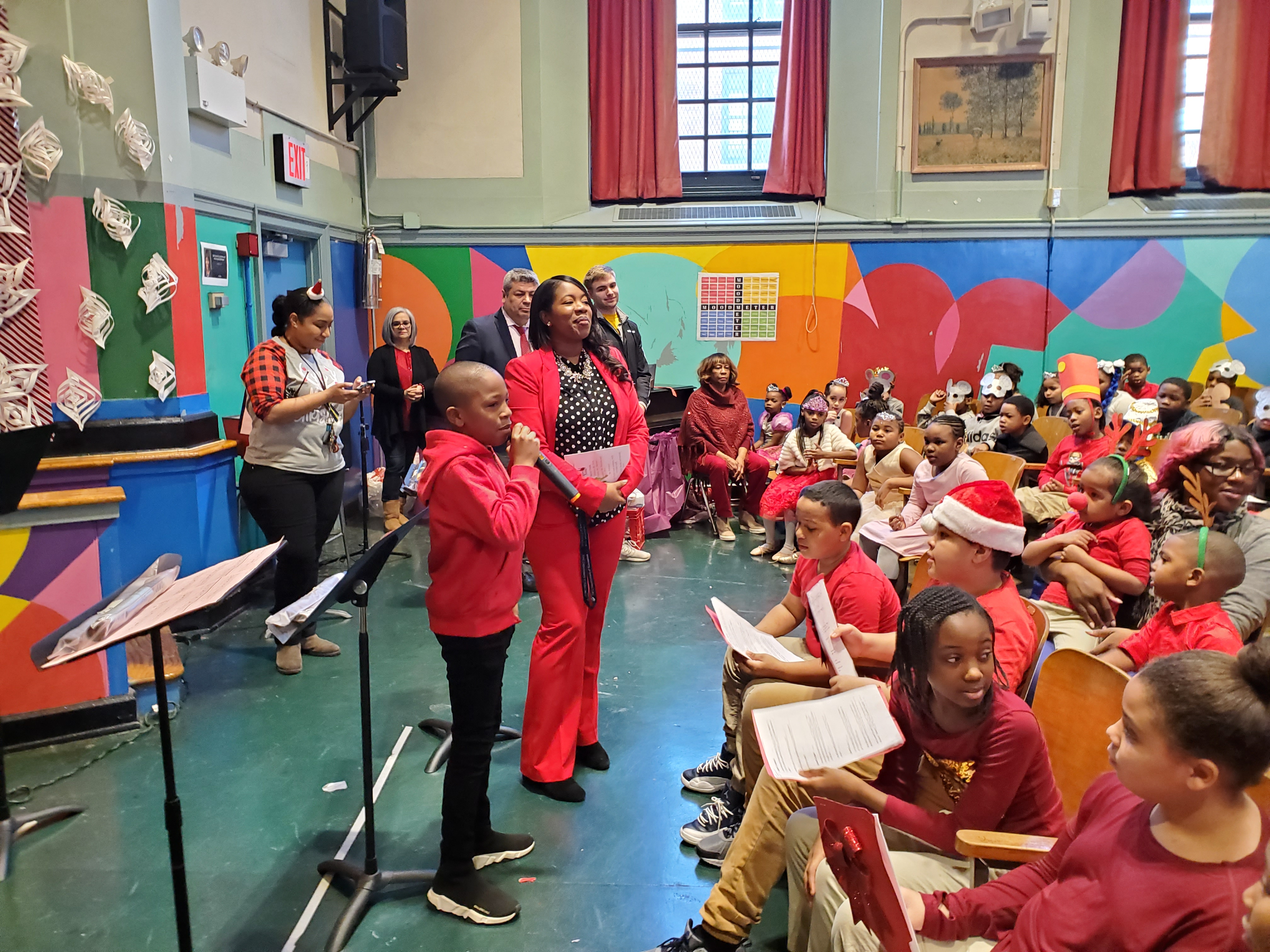 Students dressed in red and talking on microphone during Holiday show.
