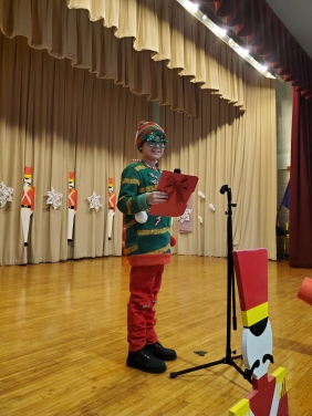 Student in elf costume standing on stage and smiling at camera
